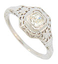 Basket filigree and full figured blooms adorn the sides and shoulders of this glittering antique engagement ring