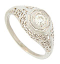 An intricate organic filigree adorns the shoulders and sides of this 14K white gold antique engagement ring