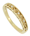 A bold floral filigree fashioned of 14K yellow gold adorns the surface of this antique style wedding band