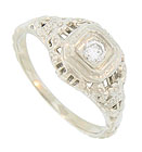 Delicate organic engraving and simple horizontal filigree adorn the sides and shoulders of this antique engagement ring