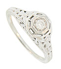 A luminous .08 carat, H color, Si1 clarity round cut diamond is set into the face of this 14K white gold engagement ring