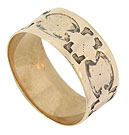 An intricate hand hammered pattern of organic figurals adorn the face of this 14K red gold antique wedding band