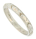 A romantic pattern of deeply engraved squash blossoms dances across the face of this antique platinum wedding band