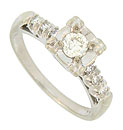 Sparkling trios of fine faceted diamonds are set into pinched petaled mountings on the shoulders of this 14K white gold vintage engagment ring