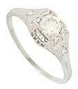 Trios of diamonds are set in the shoulders of this 14K white gold antique style engagement ring