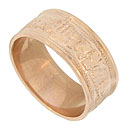 A tumbling pattern of grapes and leaves adorns the surface of this 14K red gold wedding band