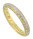 Intricate organic engraving covers the face and sides of this stunning 18K gold vintage wedding band