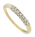 A string of seven dazzling fine faceted diamonds are set into abstract floral mountings on the face of this 14K gold estate wedding band