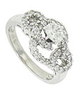 Open ribbons of cutwork set with .70 total weight of sparkling diamonds spin around the shoulders and face of this magnificent 14K white gold engagement ring