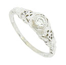 Elegant organic cutwork and intricate engraving adorn the shoulders and sides of this antique engagement ring