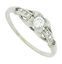 A fiery .15 carat round cut diamond is set into the face of this 18K white gold engagement ring