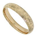 This antique bangle bracelet is crafted of 14K yellow gold and embellished with elegant floral engraving and scrollwork