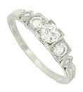 A dazzling .36 carat, round cut diamond rises above the face of this 18K white gold antique engagement ring