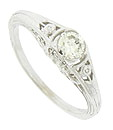 Romantic floral cutwork adorns the shoulders and sides of this 14K white gold engagement ring