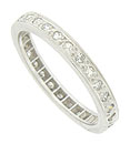 This elegant platinum estate wedding band is adorned with a twisting engraved pattern