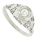 Intricate filigree and abstract floral engraving adorn the sides and shoulders of this phenomenal antique engagement ring