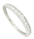 A dazzling string of princess and emerald cut diamonds are bezel set in the face of this elegant estate wedding band