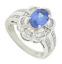 A glorious oval cut tanzanite bursts from the center of this floral inspired engagement ring