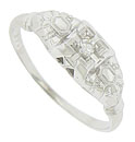 Intricate abstract engraving adorns the face and shoulders of this 14K antique engagement ring