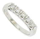Abstract floral mountings cradle sparkling round cut diamonds on the face of this 14K white gold wedding band