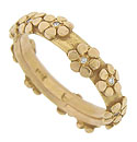 Flirty flowers set with fine faceted diamonds tumble across the surface of this 14K yellow gold estate wedding band