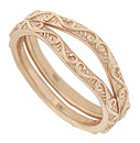 These curved 14K rose gold antique style wedding bands are covered with curling vines and leaves