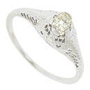 Ribbons of intricate engraving drape from the center mount of this remarkable 14K white gold engagement ring