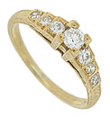 This spectacular 18K yellow gold engagement ring features a stepped mounting set with an array of brilliant round cut diamonds