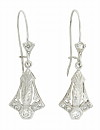 Elongated diamond frosted flowers present an organic engraved figure on these antique  dangle earrings