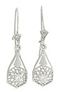 Elongated diamond frosted flowers present a dangling figural star set with a single fine faceted diamond on these antique style earrings