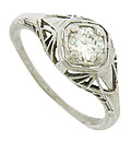 A bold web of triangular filigree radiates from the square face of this 18K white gold antique style engagement ring