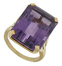 This exceptional 14K yellow gold estate ring features a deep violet emerald cut amethyst set into its face