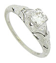Intricate engraving and organic cut-work adorn the sides and shoulders of this exquisite antique style engagement ring