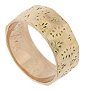The faceted surface of this antique wedding band is engraved with a pattern of abstract flowers and fleur de lis figures