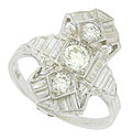 A trio of dazzling, round cut diamonds are set into the face of this phenomenal Art Deco engagement ring