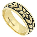 Large delicately engraved blooms and leaves seem to burst from the face of this romantic 14K yellow gold wedding band