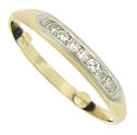 This sparkling vintage wedding band is fashioned of 14K yellow gold and features ribbon of frosted white gold, channel set with seven round cut diamonds
