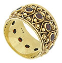 This unique 14K yellow gold estate wedding band is adorned with bezel set garnets wrapped in triangular figures of golden yarn