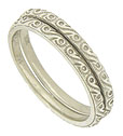 Abstract engraving and impressed milgrain adorn the surface of these 14K white gold stackable wedding bands