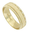 Organic engraving and impressed milgrain accent the edges of this 14K yellow gold wedding band