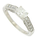 Strings of sparkling, round cut diamonds adorn the sides and shoulders of this spectacular 14K white gold engagement ring