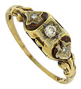 Diamond studded fleur-de-lis designs decorate the shoulders of this 14K rose gold vintage engagement ring