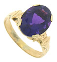 A bold faceted 1.65 carat oval cut amethyst is set into the face of this elegant 10K rose gold antique ring