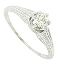 Intricately engraved leaves on the shoulders of this antique engagement ring serve to present a