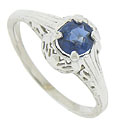 Abstract organic cutwork adorns the sides and shoulders of this antique engagement ring