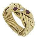 A brilliant round cut diamond is flanked by rubies set into the face of this unique 14K yellow gold puzzle ring