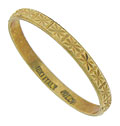 Deeply impressed abstract flowers dance around the surface of this 18K yellow gold wedding band