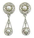 These antique earrings are fashioned of platinum and set with cultured pearls and fine faceted diamonds