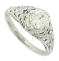 Magnificent floral cutwork, intricate engraving and weblike filigree adorn the surface of this dazzling 14K white gold engagement ring