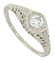 Abstract organic engraving and floral cutwork adorn the sides and shoulders of this antique style engagement ring